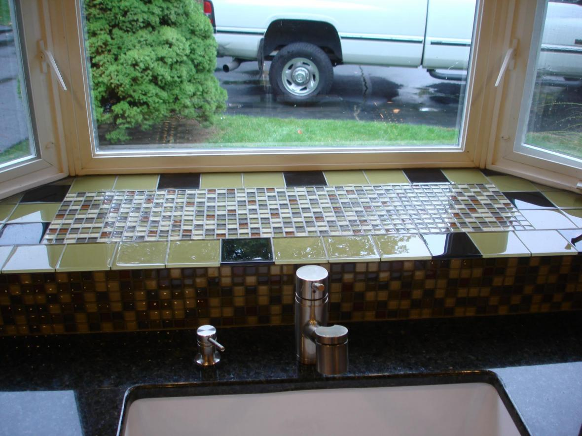 Glass mossaic kitchen backsplash behind sink bay window