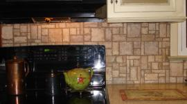 Mosaic stone pattern backsplash stove view