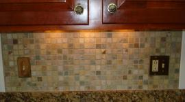 Stone mossaic backsplash with metal decos