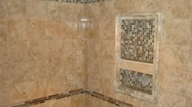 Porcelain tile shower with glass and slate borders and niche