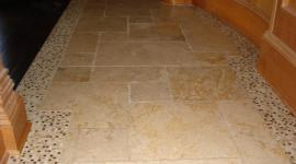 Tumbled marble with marble mosaic border in foyer